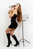 Portrait of a singing beautiful woman in black dress