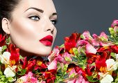 High fashion model girl with colorful flowers and red lips. Vogue style woman portrait. Beautiful face makeup. Glamorous lady. Vivid colours