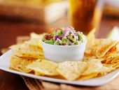 guacamole in small condiment cup with tortilla chips and beer