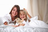 Woman and young girl lying in bed smiling, isolated
