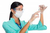 Doctor wearing a mask prepares a syringe for injection
