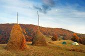 Autumn landscape. Haystack on the meadow. Tourist tent in a mountain village. Carpathians, Ukraine, Europe