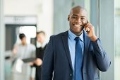 cheerful african businessman talking on cell phone in office