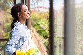 cheerful young african housewife looking through the window