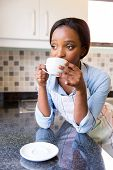 thoughtful african housewife drinking coffee in the morning