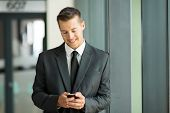 happy businessman texting on his smart phone