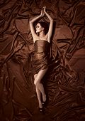 Beautiful woman lying on a chocolate fabric.
