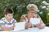 Granny with grandson watching tablet in nature
