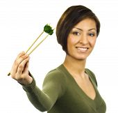 Smiling Young Woman Holds A Piece Of Green Broccoli With Chopsticks