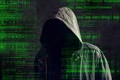 stock photo of incognito  - Faceless hooded anonymous computer hacker with programming code from monitor - JPG