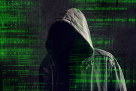 picture of incognito  - Faceless hooded anonymous computer hacker with programming code from monitor - JPG