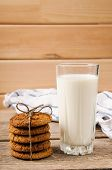 picture of milk glass  - rustic oatmeal cookies on a wooden table with a glass of milk - JPG