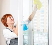 stock photo of window washing  - Mature woman cleaning window - JPG