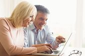 foto of maturity  - Happy mature couple using laptop at home in the kitchen - JPG