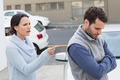 foto of argument  - Young couple having an argument outside their car - JPG