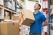 stock photo of worker  - Side view of worker with backache while lifting box in the warehouse - JPG