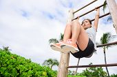 foto of abs  - Core cross training fit woman doing abs exercises on beach on fitness vertical ladder rack - JPG