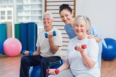 picture of senior class  - Portrait of happy female instructor with senior couple in gym - JPG