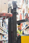 stock photo of forklift driver  - Focused driver operating forklift machine in warehouse - JPG