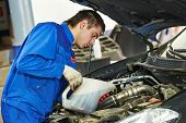 picture of lubricant  - auto mechanic technician replacing and pouring motor oil into automobile engine at maintenance repair service station - JPG