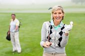 image of ladies golf  - Lady golfer smiling at camera with partner behind on a foggy day at the golf course - JPG