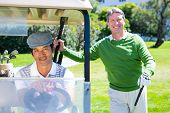stock photo of buggy  - Happy golfing friends setting out smiling at camera on buggy at golf course - JPG