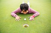 pic of cheater  - Golfer trying to flick ball into hole at the golf course - JPG
