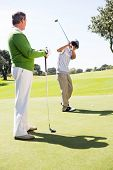 picture of take off clothes  - Golfing friends teeing off at the golf course - JPG