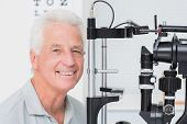 picture of slit  - Portrait of happy senior man in front of slit lamp at clinic - JPG