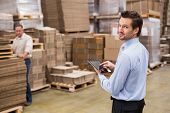 stock photo of warehouse  - Warehouse manager working on tablet pc in a large warehouse - JPG