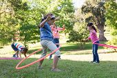 image of hula hoop  - Little friends playing with hula hoops in park on a sunny day - JPG