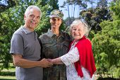 foto of reunited  - Soldier reunited with her parents on a sunny day - JPG