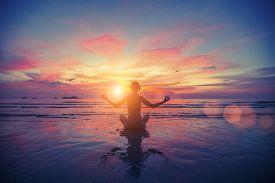image of mudra  - Woman doing meditation near the ocean beach - JPG