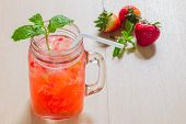 stock photo of infusion  - Strawberry infused water with mint on wooden table - JPG