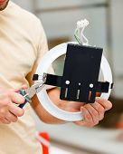 stock photo of pliers  - Electrician working with pliers mounting a light - JPG