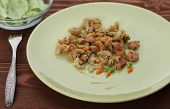 picture of green pea  - Wholegrain rigatoni with green peas and carrot and chicken sausage on green plate in background is salad - JPG