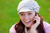 Happy young woman on phone sitting on the grass