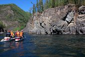 picture of raft  - Team of people on an inflatable catamaran raft on a river canyon - JPG