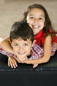 stock photo of brother sister  - Cute brother and sister sitting on a couch - JPG