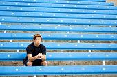 stock photo of bleachers  - Male athlete sitting in the bleachers - JPG