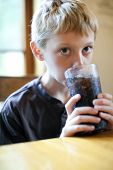 Little boy drinking a glass of soda