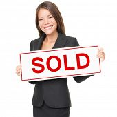Real estate agent holding sold sign isolated on white background. Beautiful cheerful Asian / Caucasi