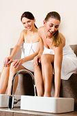 Two women presumably best friends - taking a footbath