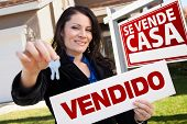 Happy Attractive Hispanic Woman Holding Vendido Real Estate Sign and Keys in Front Se Vende Casa Rea
