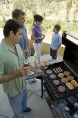 picture of niece  - A family gathers around the BBQ grill to cook some burgers and hot dogs