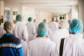 Group Of People In Industrial Production. People Go Back To The Camera In White Gowns And Shoe Cover poster