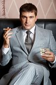 Portrait of handsome man in grey suit sitting on leather sofa with whisky and cigar in casino