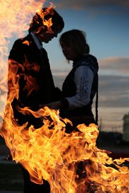 image of hot couple  - Embracing couple silhouette behind fire - JPG