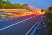 Highway At Twilight With Light Trails. High Traffic Road With Automobile Light Trails. poster