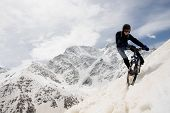 YOUNG MAN BIKING DOWN SNOWY SLOPE